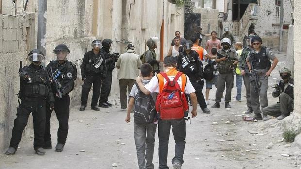 Palestinian school children walk past Israeli riot police